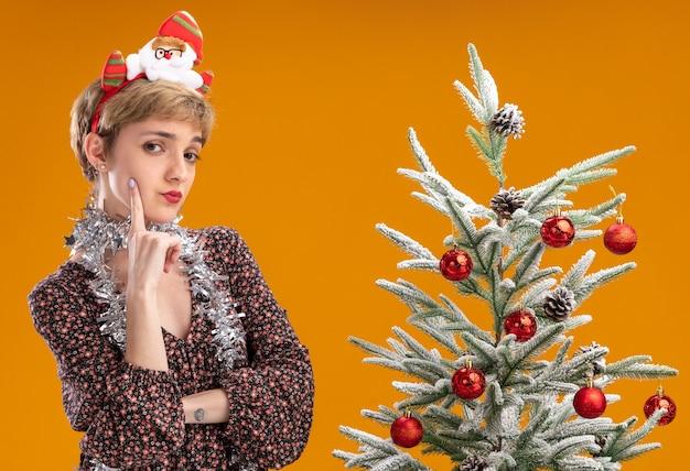 オレンジ色の背景で隔離の顔に触れるカメラを見て装飾されたクリスマスツリーの近くに立っている首の周りにサンタクロースのヘッドバンドと見掛け倒しの花輪を身に着けている疑わしい若いかわいい女の子