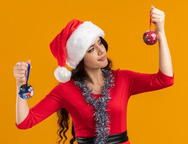 Dubbiosa giovane bella ragazza che indossa cappello da babbo natale e ghirlanda di orpelli intorno al collo tenendo palline di natale guardando uno di loro isolato sulla parete arancione