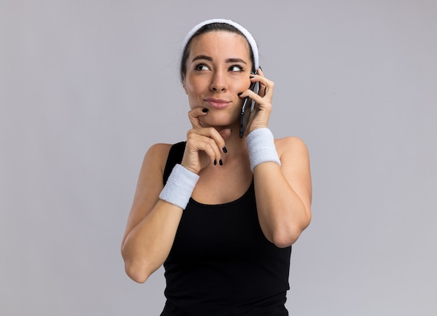 Dubbiosa giovane ragazza piuttosto sportiva che indossa fascia e braccialetti che parla al telefono tenendo la mano sul mento guardando in alto