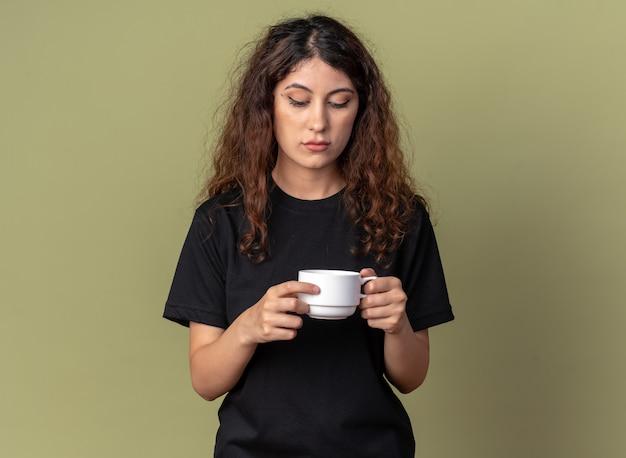 Сомнительная молодая красивая женщина, держащая чашку чая, смотрящую внутрь, изолированную на оливково-зеленой стене с копией пространства