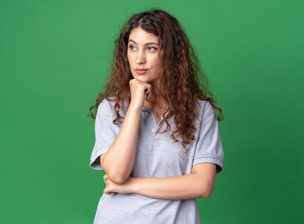 Dubbiosa giovane donna graziosa che tiene la mano sul mento guardando il lato isolato sulla parete verde con spazio di copia