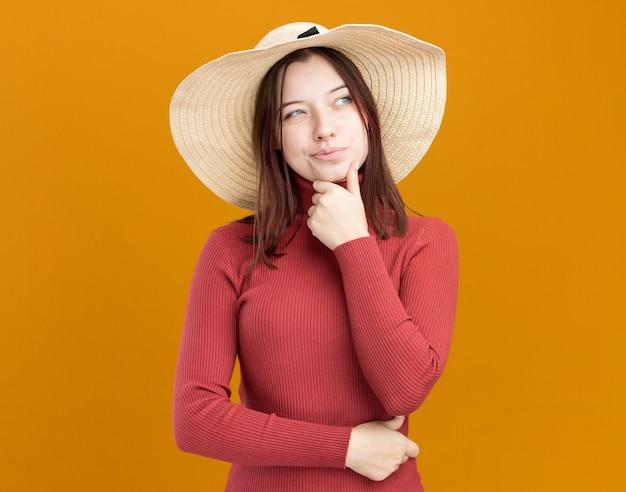 オレンジ色の壁で隔離された側を見ているあごに手を保つビーチ帽子をかぶっている疑わしい若いきれいな女性
