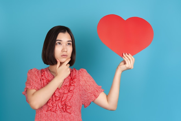 Doubting, hesitant young asian woman in red dress holds a large red paper heart and rubs her chin
