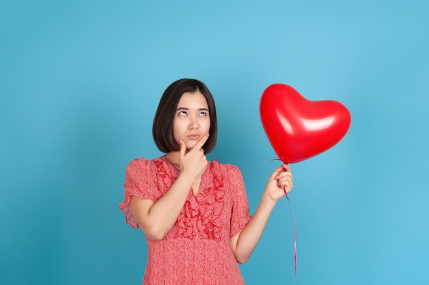 Doubting young asian woman in a red dress looks sideways, holds a flying red heart-shaped balloon