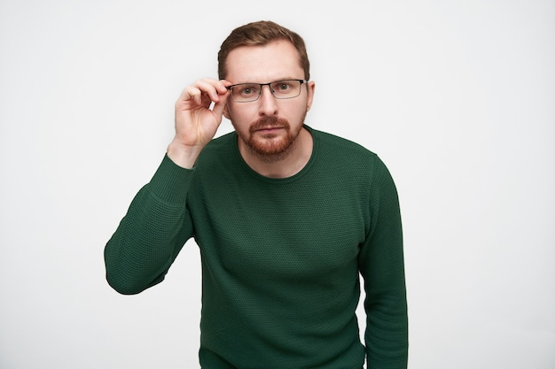 Doubting young brunette short haired pretty male with beard looking attentively and holding hand on his eyewear, posing in casual clothes