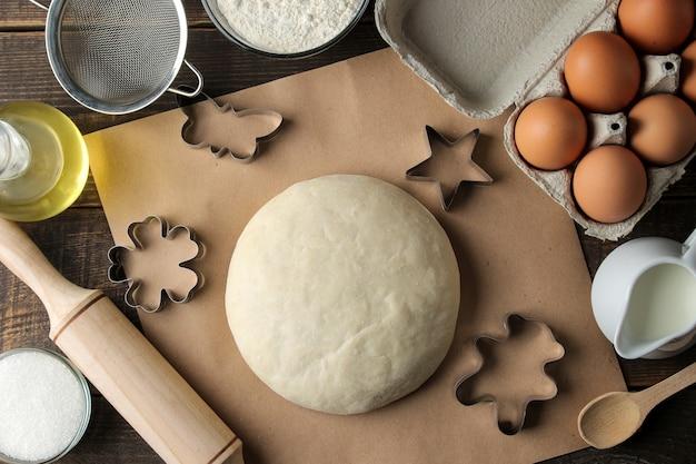 반죽 및 베이킹 재료 비스킷 형태와 갈색 나무 테이블에 베이킹 도구.