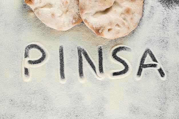 검은 배경에 텍스트 핀사가 있는 반죽과 밀가루. pinsa romana 및 scrocchiarella 미식 이탈리아 요리. 이탈리아의 전통 요리.