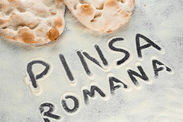 검은 배경에 핀사 로마나 이탈리아노라는 텍스트가 있는 반죽과 밀가루. scrocchiarella 미식 이탈리아 요리. 이탈리아의 전통 요리.