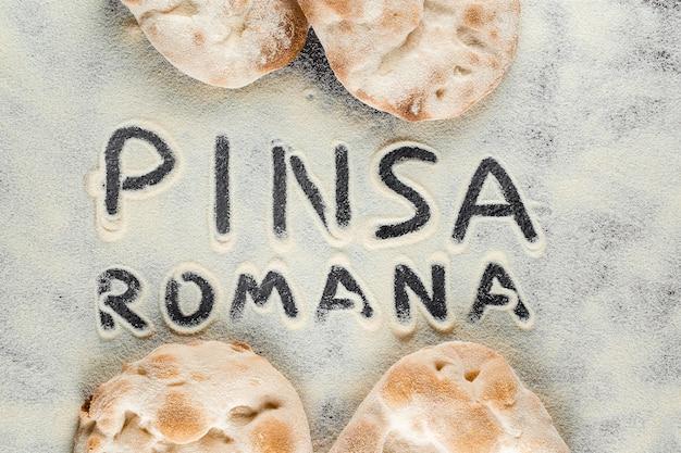 검은 배경에 핀사 로마나라는 텍스트가 있는 반죽과 밀가루. scrocchiarella 미식 이탈리아 요리. 이탈리아의 전통 요리.