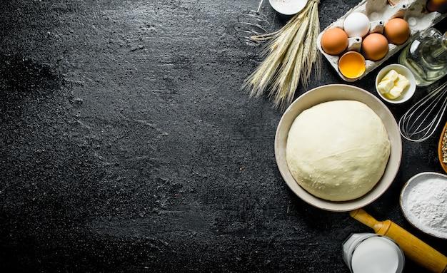 生地の背景。卵、小麦粉、バターをまぶした生地。黒の素朴なテーブルの上