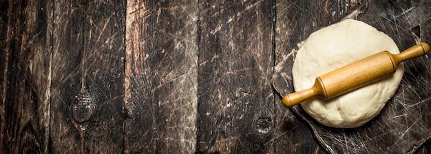 生地の背景。木製の背景に麺棒で新鮮な生地。