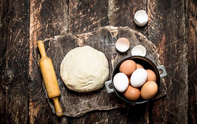 生地の背景。素朴なテーブルの古い木の板にめん棒と新鮮な卵が付いている生地。