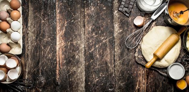 生地の背景。めん棒と具材が入ったペストリー。木製のテーブルの上。