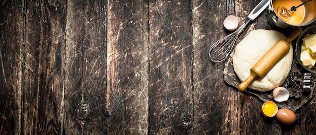 生地の背景。木製のテーブルに麺棒と材料が入ったペストリー。