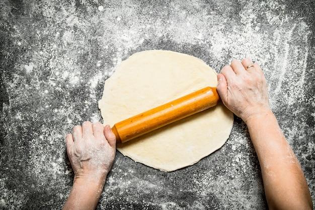 반죽 배경. 소박한 테이블에 쿠키에 대한 여성의 손 롤링.