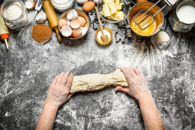 Dough background. woman kneads dough with various ingredients on the table. on rustic background .