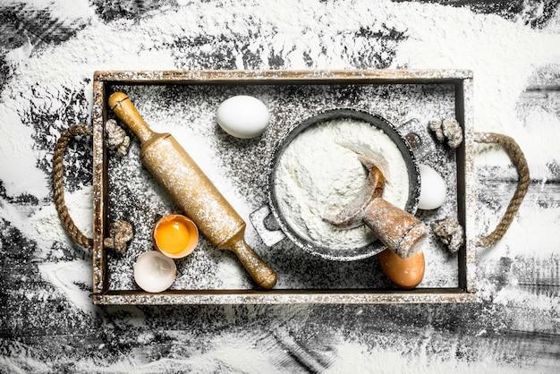 生地の背景石のテーブルに卵と麺棒で小麦粉