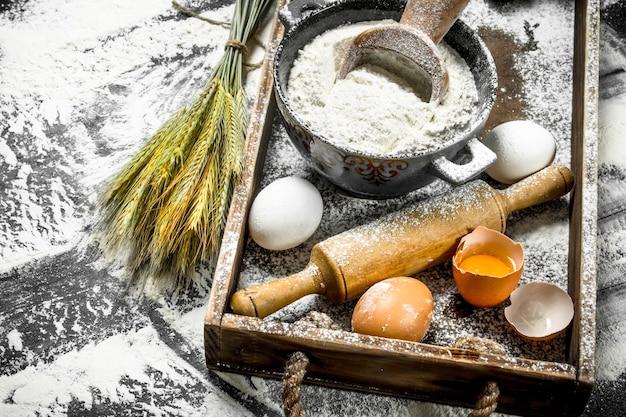 生地のバックラウンド。卵とめん棒で小麦粉。石のテーブルの上。