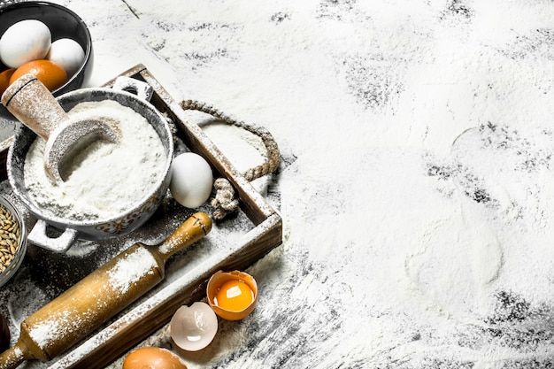 生地のバックラウンド。卵とめん棒で小麦粉。木箱に。