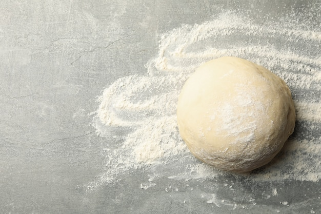 Dough ball and flour on gray background