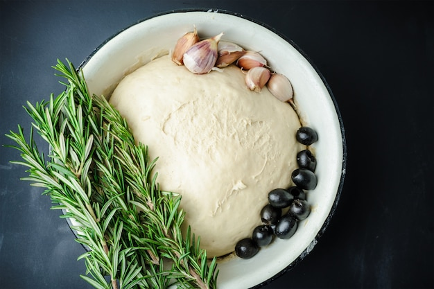 Dough in a bowl, fresh rosemary, garlic and olives on a black table