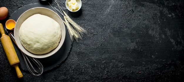 The dough in a bowl with a rolling pin, spikelets and eggs on black rustic table