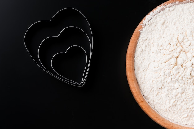 Dough cutter in shape of heart and a bowl with flour on black table. valentines day baking background