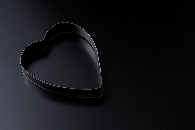 Dough cutter in shape of heart on a dark background with copy space. valentines day background