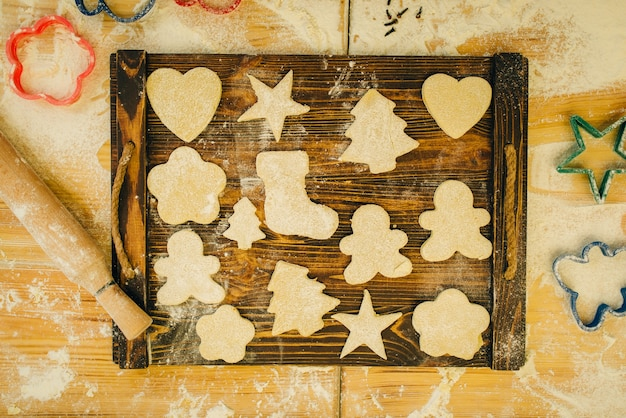 The dough in different forms cuted out by cookie cutters on wooden board, top view, nobody. hearts, stars and gingerbread man, pastry templates on the table