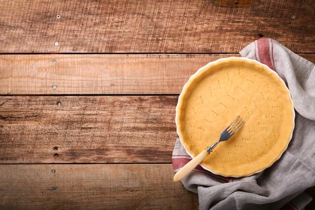 키시, 타르트 또는 파이를 세라믹 베이킹 형태로 굽기 위한 반죽은 오래된 소박한 판자 나무 배경 위에 키친 타올에 굽기 위한 준비가 되어 있습니다. 상위 뷰, 복사 공간입니다. 휴가를 위한 개념 수제 베이킹.