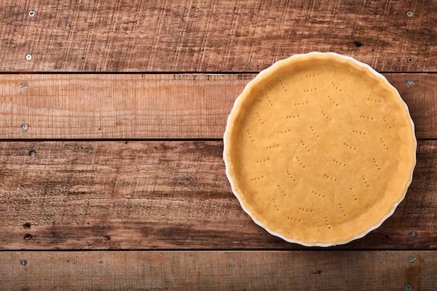 古い素朴な板の木製の背景の上にキッチンタオルで焼く準備ができているセラミックベーキングフォームでキッシュ、タルトまたはパイを焼くための生地。上面図、コピースペース。休日のコンセプト自家製ベーキング。