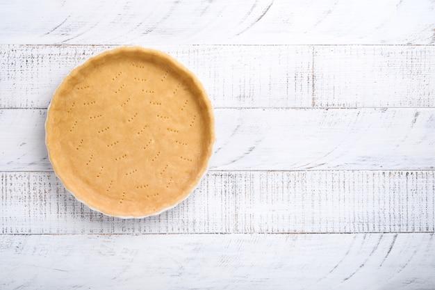 키시, 타르트 또는 파이를 세라믹 베이킹 형태로 굽기 위한 반죽은 흰색 오래된 소박한 판자 나무 배경 위에 키친 타올에 굽기 위한 준비가 되어 있습니다. 상위 뷰, 복사 공간입니다. 휴가를 위한 개념 수제 베이킹.
