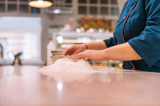 クロワッサン生地。クロワッサンの生地を作る青いジャケットを着た勤勉な経験豊富なパン屋