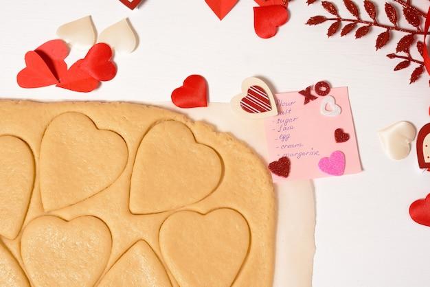 Тесто для печенья сердечка на день всех влюбленных, ингредиенты для выпечки к празднику. декоративные сердца вид сверху.