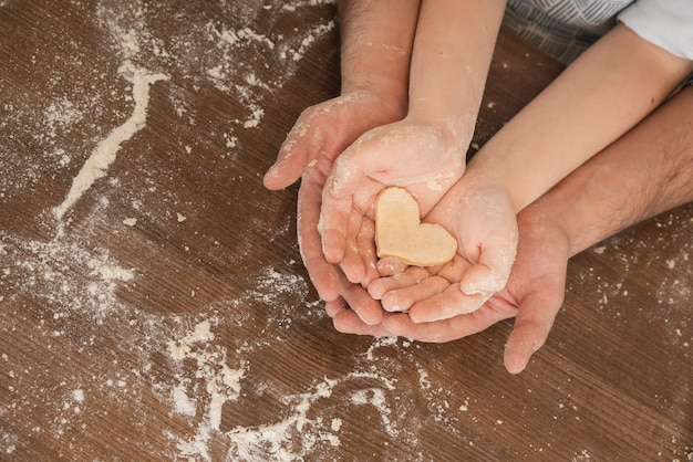 Dough heart shape in father and son hands
