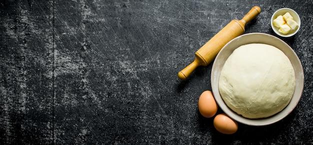 素朴なテーブルの上に卵、麺棒、バターを入れたボウルの生地