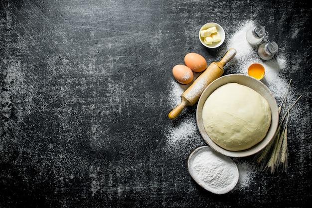 小麦粉、卵、バターを入れたボウルの生地。暗い素朴な背景に