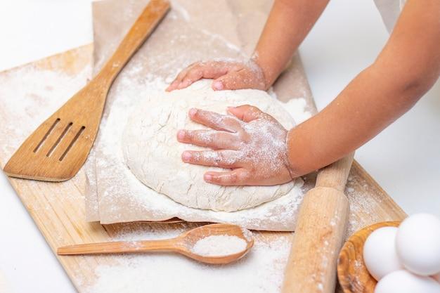 小麦粉で生地をこねる子供の手、一人の子供、子供は台所で両親を助けます