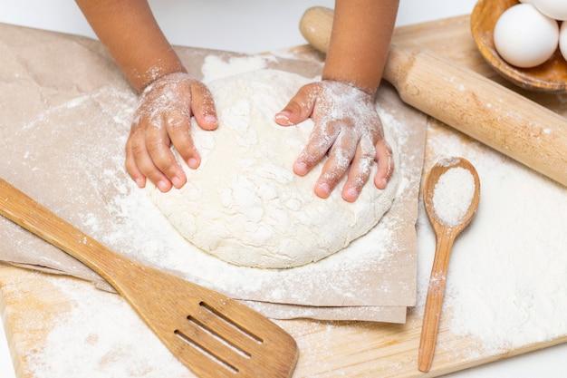 子供の手をこねる小麦粉の生地