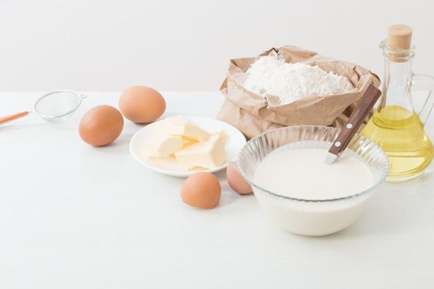 Тесто в стеклянной тарелке и продукты для его приготовления на белом