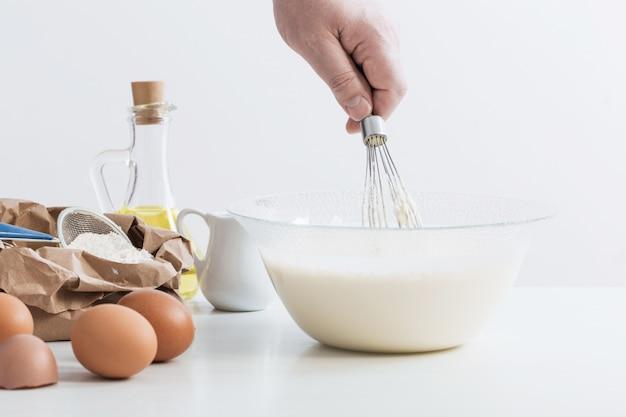 Тесто в стеклянной тарелке и продукты для его приготовления