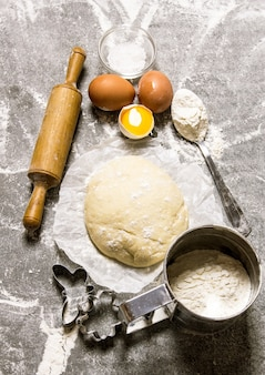 Dough and the ingredients - eggs, flour and tools - a rolling pin and shape.
