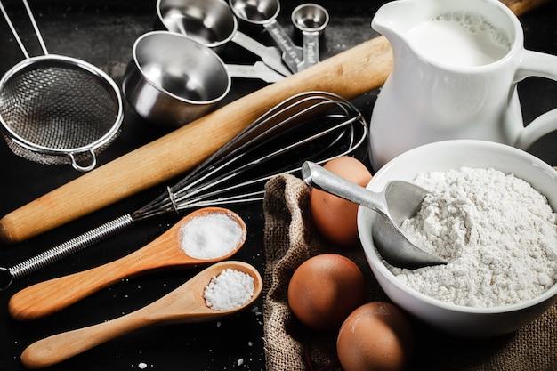 Dough ingredients and  kitchen utensils on dark