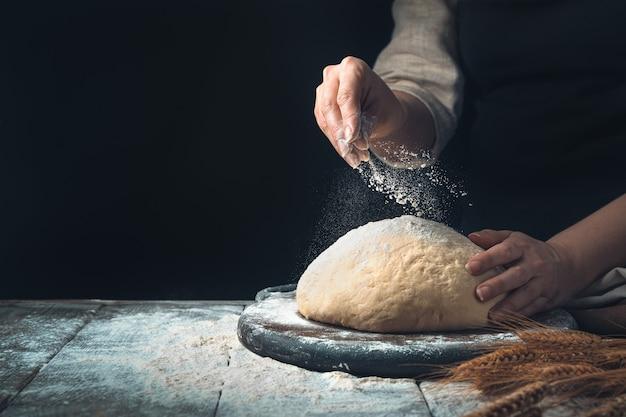Тесто посыпается рукой повара на темном фоне.