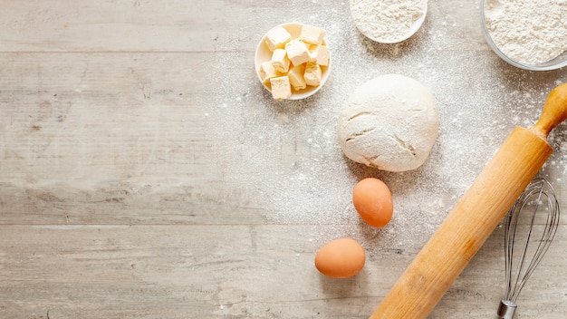 Dough kitchen roller and eggs with copy space