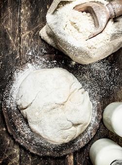 新鮮な小麦粉から作られた生地。木製のテーブルの上。