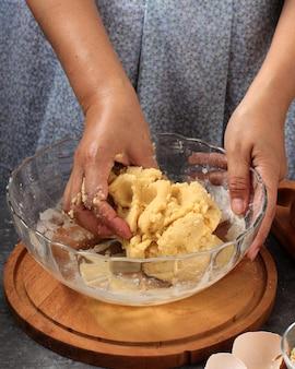 Изготовление теста, женская рука готовит тесто для выпечки хлеба в прозрачной миске на кухне
