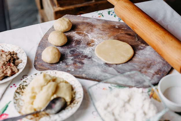 Pasta farina di pasta frolla in procinto di fare cuocere l'impasto sulla scrivania rustica in legno marrone