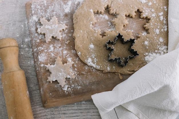 Dough near cookie cutter on chopping board