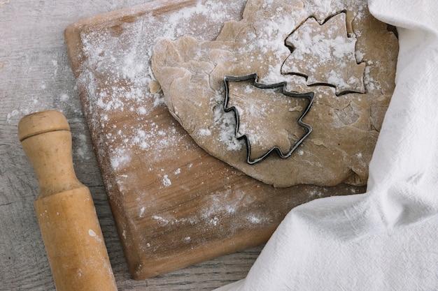 Dough near cookie cutter on cutting board